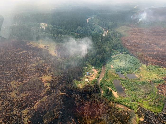 An aerial photo of a mining camp with burned areas around it.