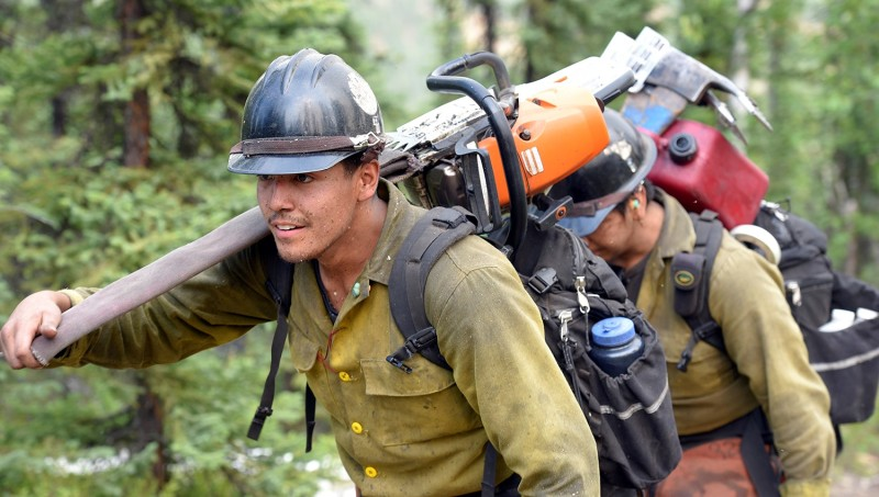 A firefighter carrying a chainsaw over his shoulder.