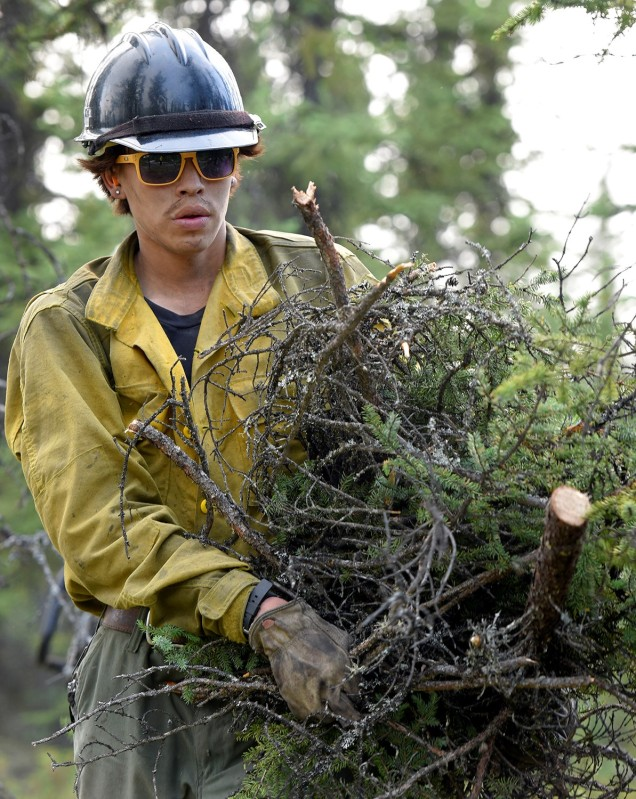 A firefighter carrying freshly cut brush.