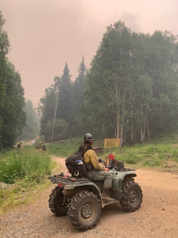 A firefighter from the Tanana Chiefs Crew sits on a four-wheeler on a road with a hose line that will serve as an anchor point to prevent the Munson Creek Fire from advancing toward Chena Hot Springs Resort. Ira Hardy/Alaska DNR-Division of Forestry