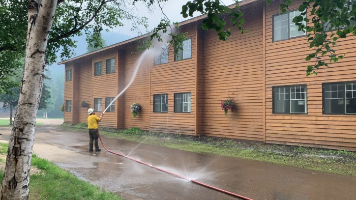 Logistics section chief Dane Smigleski sprays down the Chena Hot Springs Resort hotel with water to protect it from the advancing Munson Creek Fire on Monday evening, July 5, 2021.