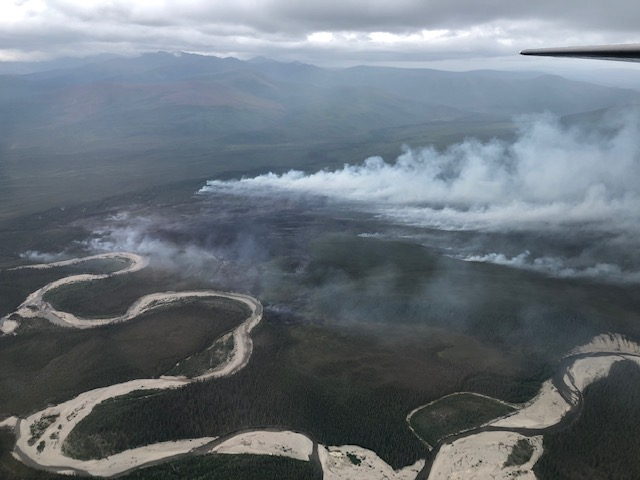 Smoke rising up from a fire burning near a river.