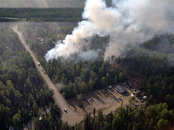 Photo of smoke rising up from the Lichen Fire burning in a forest next to a gravel road.
