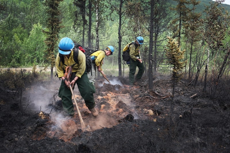 Three firefighters dig up hot spots in a burned area of the Munson Creek Fire on Wednesday, July 7.