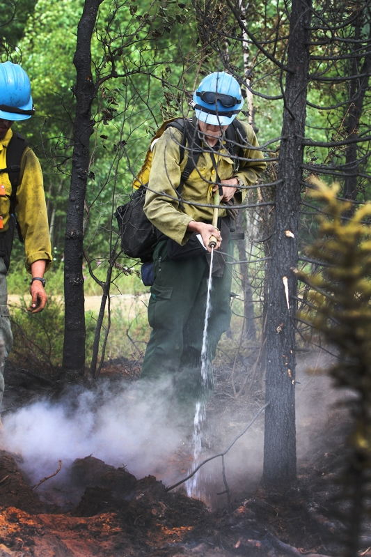 A firefighter sprays water from a portable water backpack on a hot spot of the Munson Creek Fire on Wednesday, July 7.