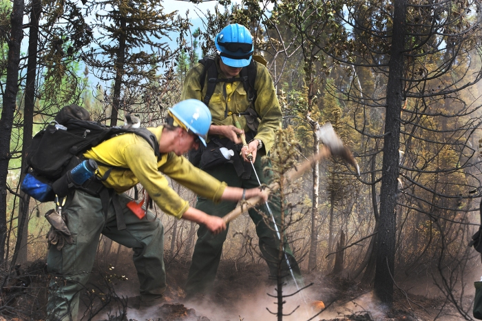 A firefighter digs up a hot spot with a pulaski while another firefighter sprays it with a hose from a portable water backpack.