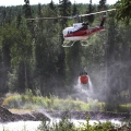 A helicopter lifts off with a full bucket of water dipped from a gravel pit.