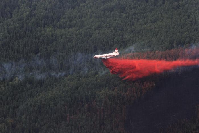 An air tanker drops a stream of red fire retardant on the Munson Creek Fire.