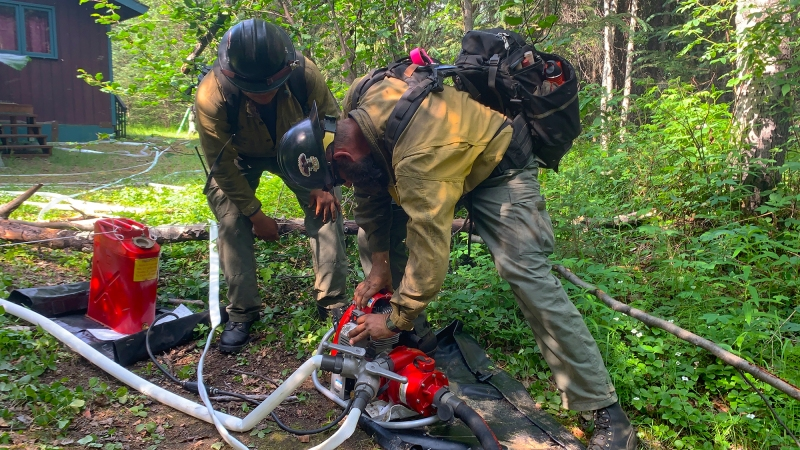Two firefighters start a pump to check a sprinkler at a cabin on the Munson Creek Fire on Sunday, July 4.