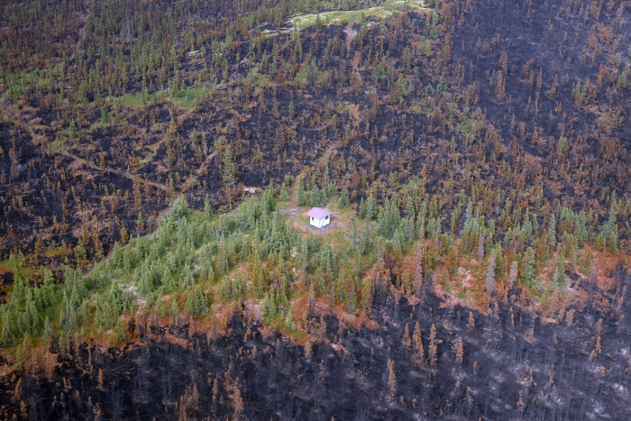The Angel Rocks to Chena Hot Springs Trail shelter stands amidst burned areas Thursday, July 8, 2021, as seen in this photo from an aerial reconnaissance flight. Fire fighters cleared brush from around the shelter before the Munson Creek Fire burned through the area. Sam Harrel/Alaska DNR-Division of Forestry