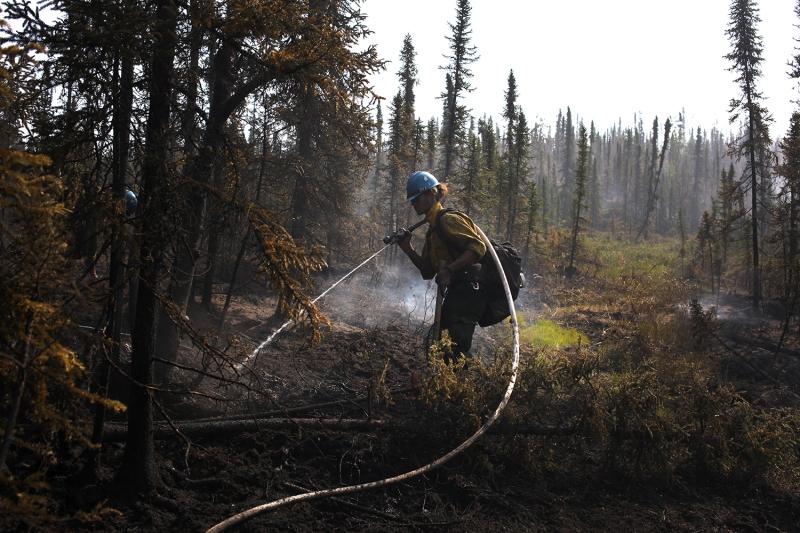 A firefighter sprays down a hot spot on the Munson Creek Fire.