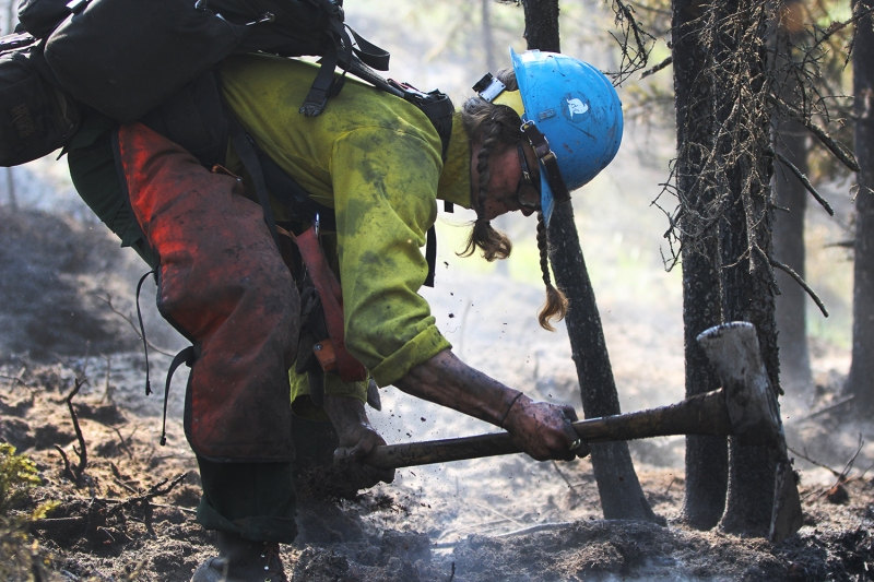A firefighter uses a pulaski to dig up a hot spot on the Munson Creek Fire