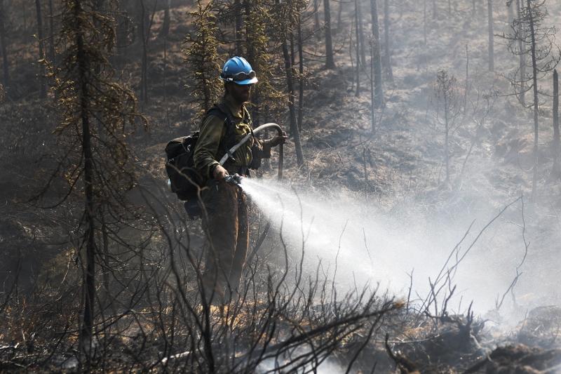 A firefighter sprays a hot spot on the Munson Creek Fire.