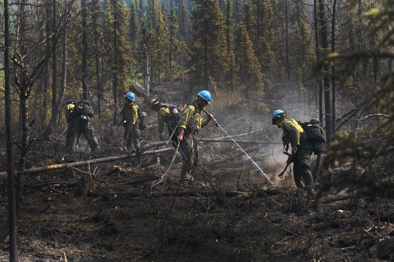 Firefighters dig up hot spots and spray water on them with a hose.