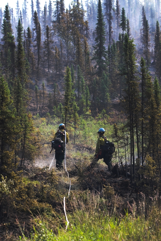 Firefighters spray hot spots with water on the Munson Creek Fire.
