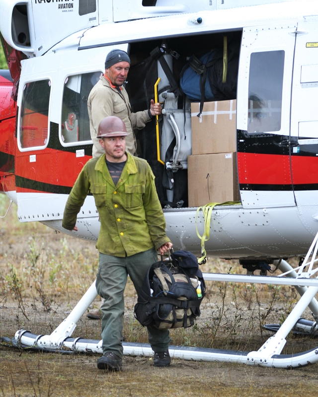 A firefighters walks away from a helicopter carrying his pack.