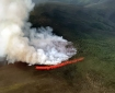 An air tanker drops a stream of red fire retardant in front of a wildfire near Dawson City, Yukon