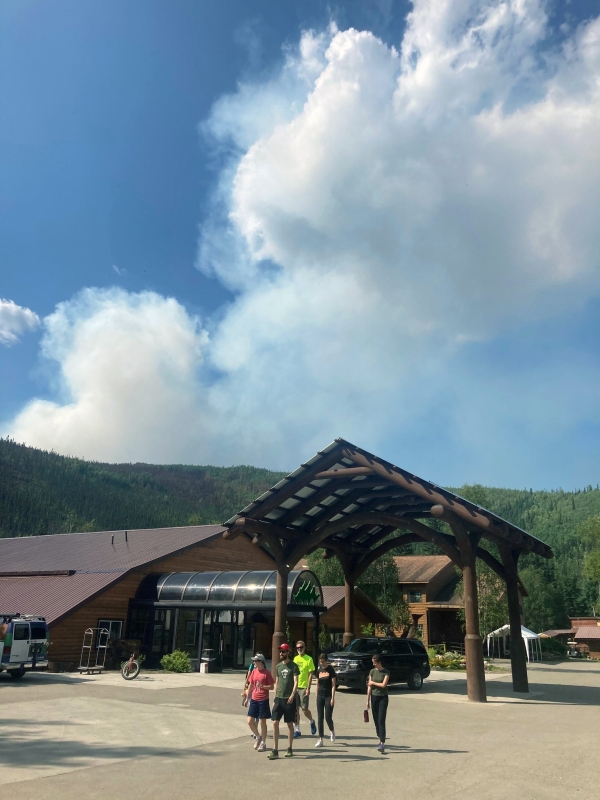 Guests walk through the parking lot at Chena Hot Springs Resort as the Munson Creek Fire puts up a smoke column south of Chena Hot Springs on Monday, July 19, 2021.
