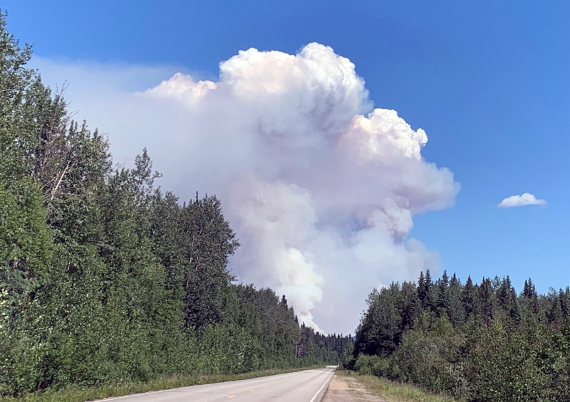 A large smoke column from the Munson Creek Fire rises into the sky at the end of Chena Hot Springs Road.