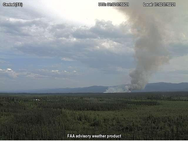 Photo of smoke rising up from forested area.