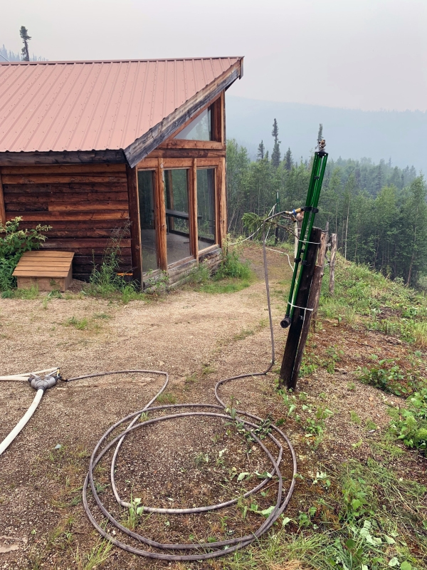 A sprinkler with a hose attached is set up on a pole near a cabin behind Chena Hot Springs Resort on Friday, July 2, 2021.