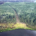 A wide saw lie cut dividing a forest from lake to a fire's edge.