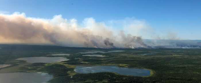 Photo of smoke drifting up from ground with lakes.