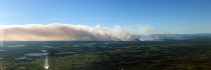 Photo of smoke drifting from land near lakes.