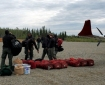 Firefighters with red gear bags unloaded from an airplane