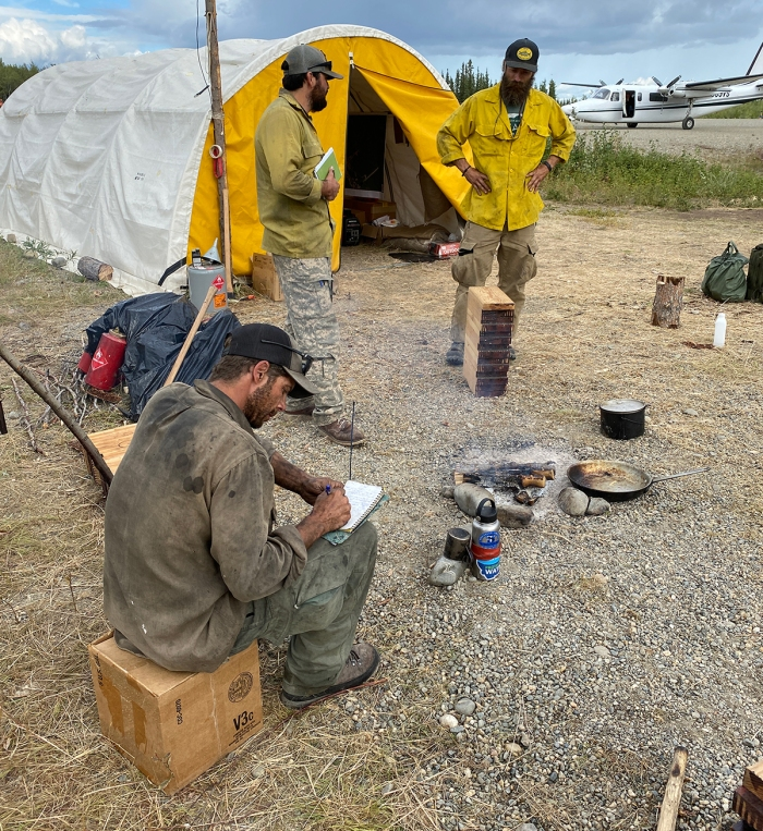 Three firefighters talking at a camp in front of a tent and an airplane.