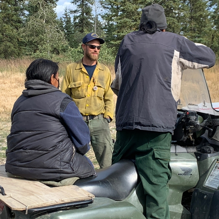 A male firefighter talking to two people on a four wheeler.