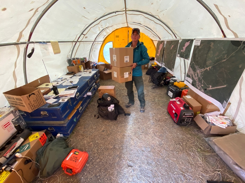 A female firefighter standing in a tent while carrying two boxes.