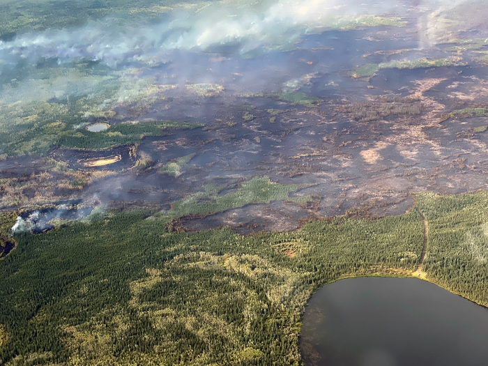 Smoke drifting up from a burned area with a lake in the bottom right corner.