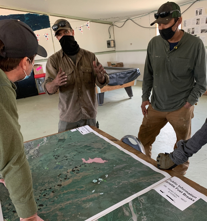 Three men talking while looking at a map on a table.
