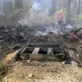 A firefighter sprays down hotspots on a wildfire behind a burned-up fish smoker.